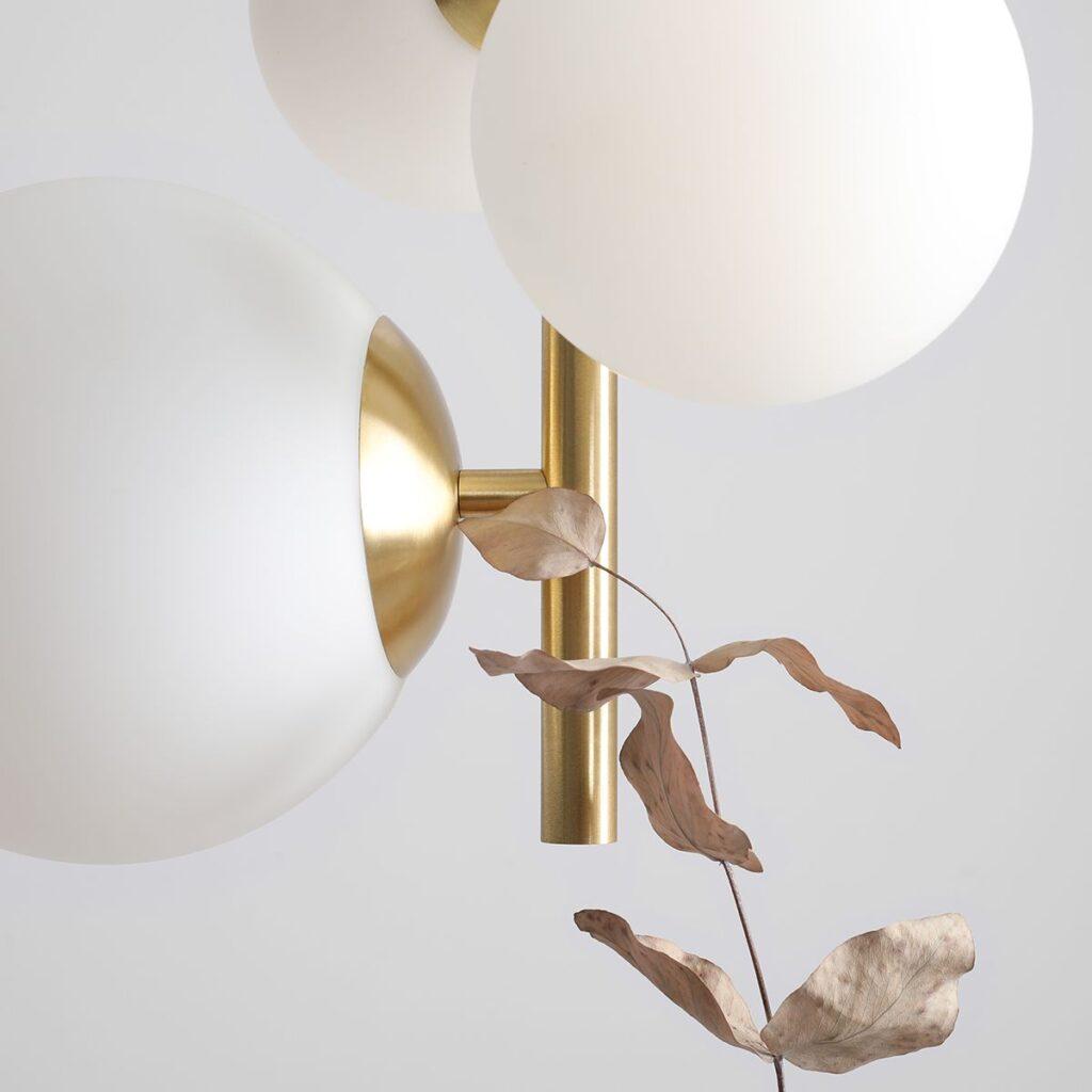 zbliżenie na lampę ze złotym wykończeniem i białymi kulami