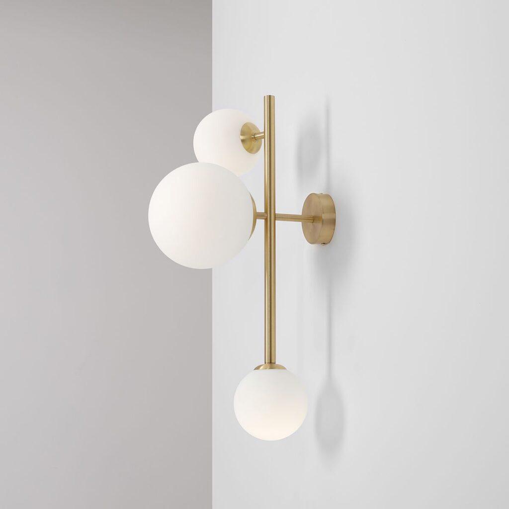 lampa ścienna z białymi kulami i złotym wykończeniem