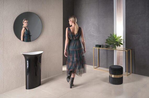 blondwłosa kobieta przechodzi przez łazienkę z elegancką czarną umywalką